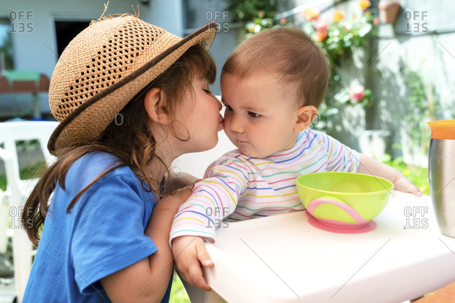 Little girl kissing her younger sister at backyard in spring