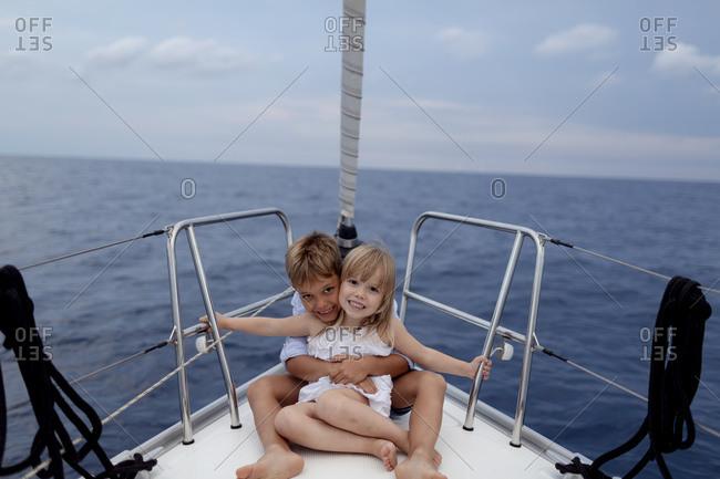 Siblings sitting on boat deck