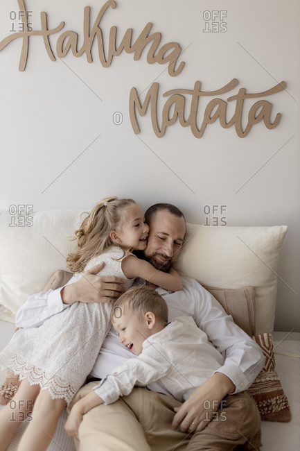 Family portrait of happy father and his two children cuddling at home