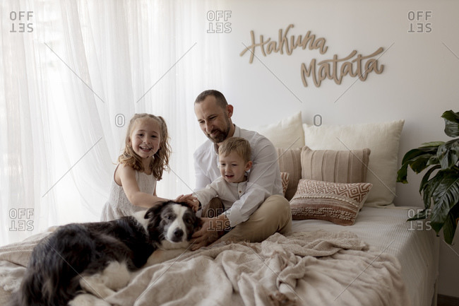 Portrait of happy father sitting on bed with his two children stroking the dog