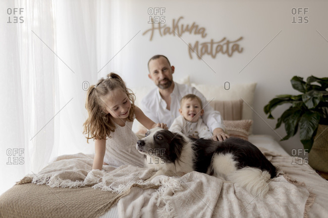 Little girl stroking her dog on bed while father and brother sitting in the background