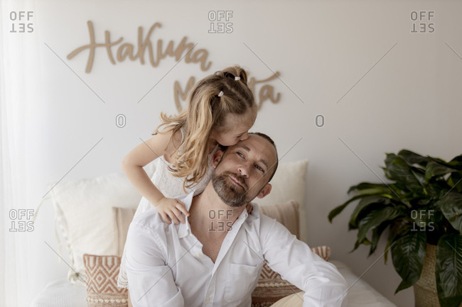 Little girl kissing her father at home