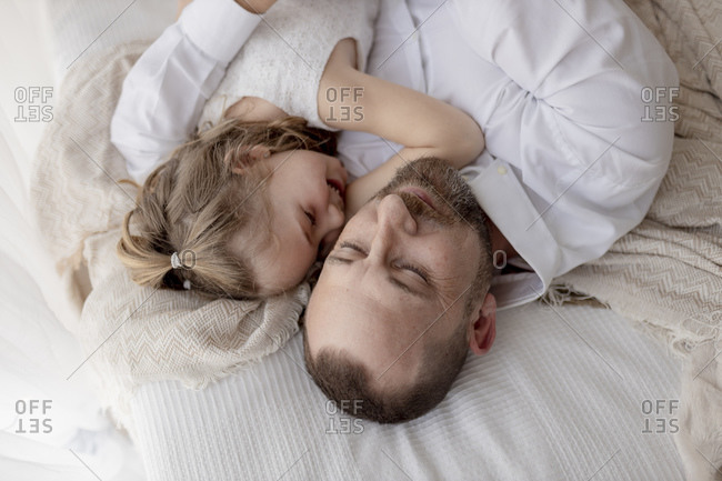 Father and little daughter resting together on bed