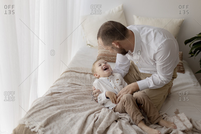 Father crouching on bed tickling his little son