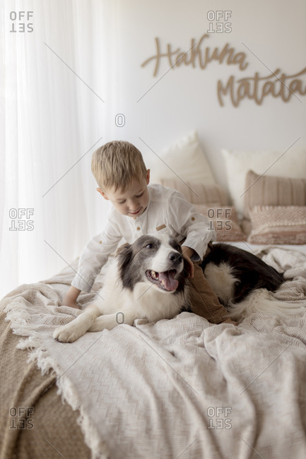 Little boy crouching on bed stroking his dog