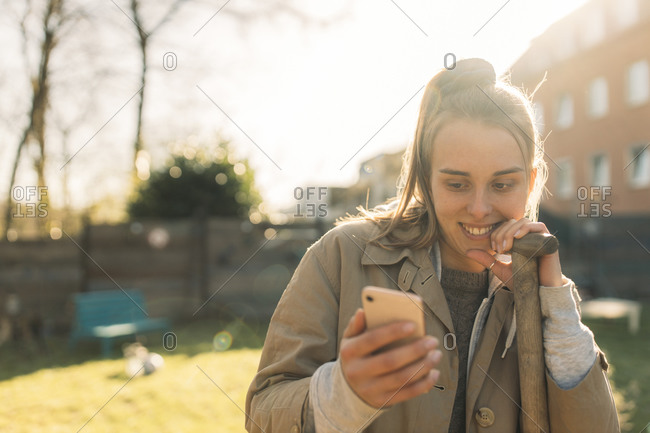 Young woman using smartphone in garden in sunshine