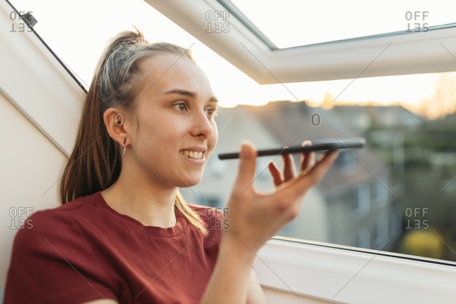 Young woman using smartphone at the window in backlight