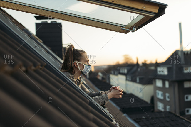 Young woman with mask looking out of window