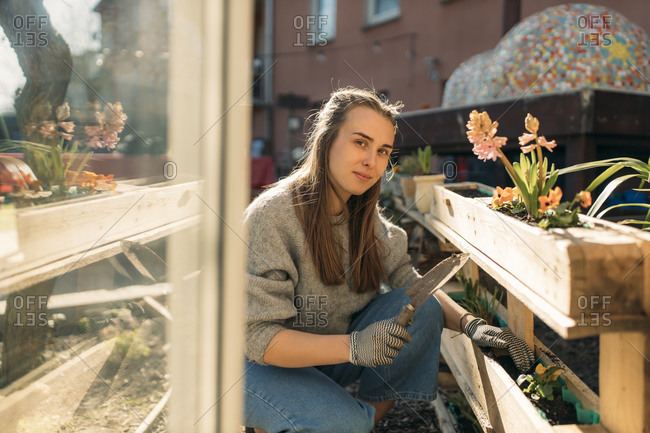 Portrait of young woman working in garden in sunshine