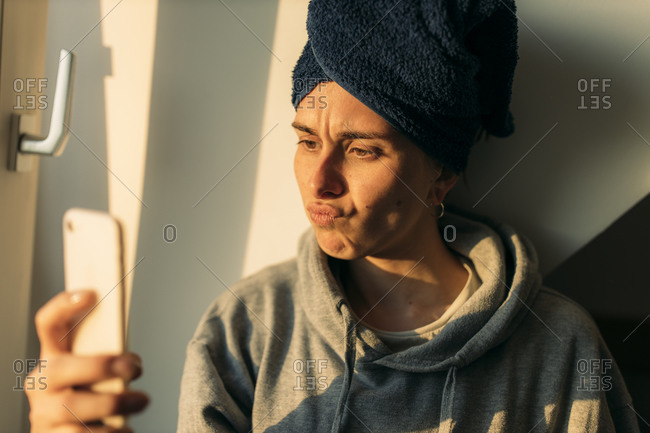 Young woman looking at cell phone at home pouting