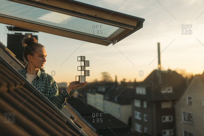 Young woman holding design at the window in the evening