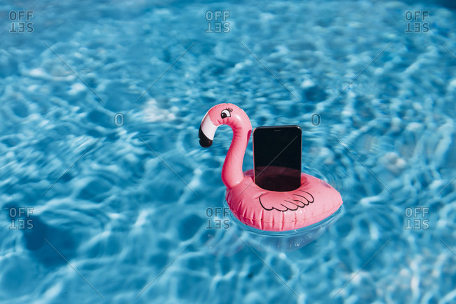 Smartphone on pink flamingo float in swimming pool