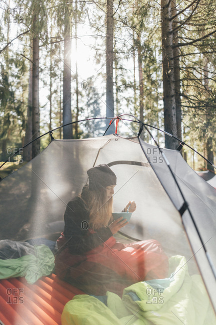 Young woman sitting in tent- eating breakfast in the forest