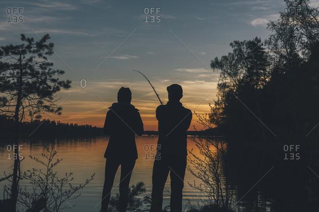 Couple standing at lake- fishing in lake at sunset