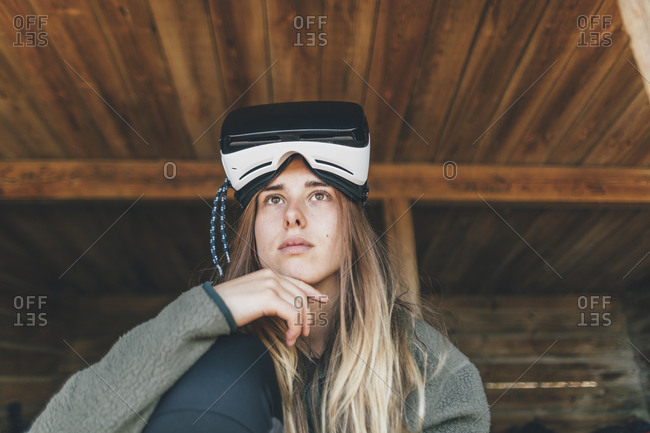 Young woman looking at distance- with VR glasses on forehead