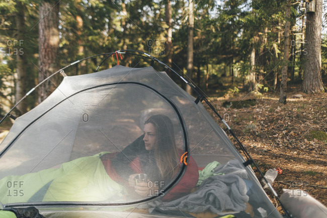 Young woman in tent is in the forest- drinking tea