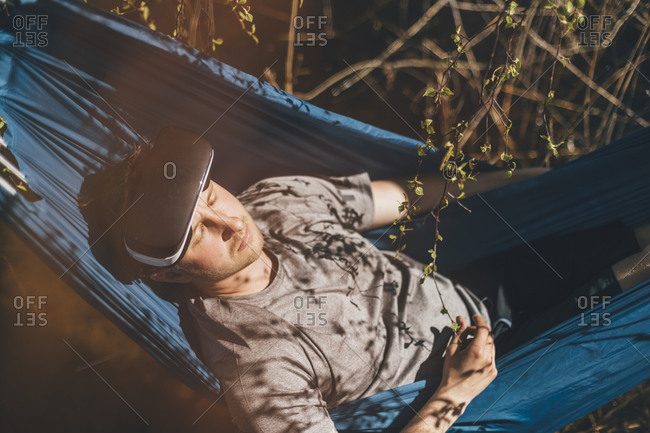 Young man relaxing in hammock- VR glasses on his forehead