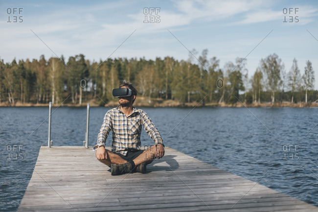 Young man sitting on jetty- wearing VR glasses
