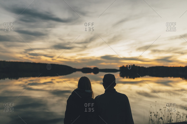 Couple sitting at lake- watching sunset