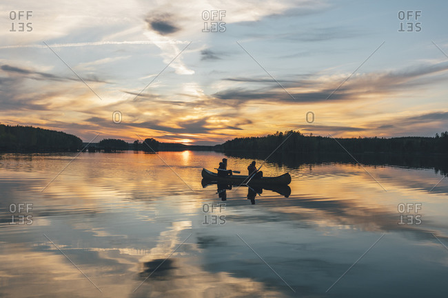 Young people boating on lake at sunset