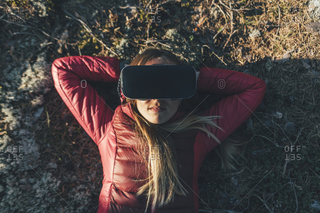 Young woman with VR goggles lying on ground in nature