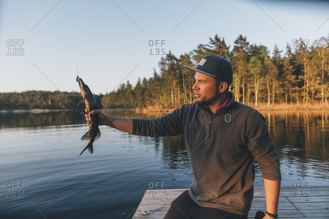 Young man holding freshly caught fish