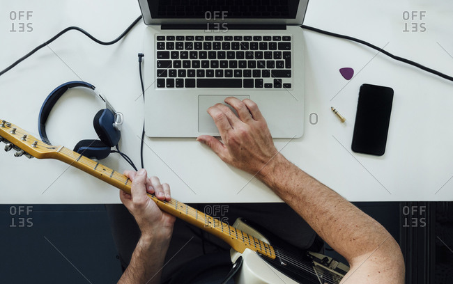 Top view of man learning to play electric guitar online using laptop