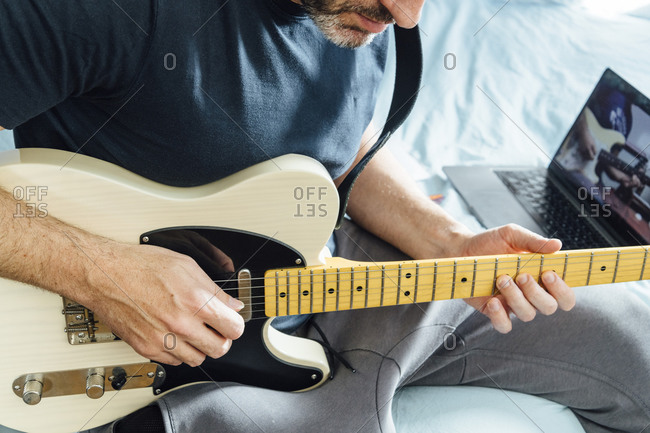 Man learning to play electric guitar online using laptop