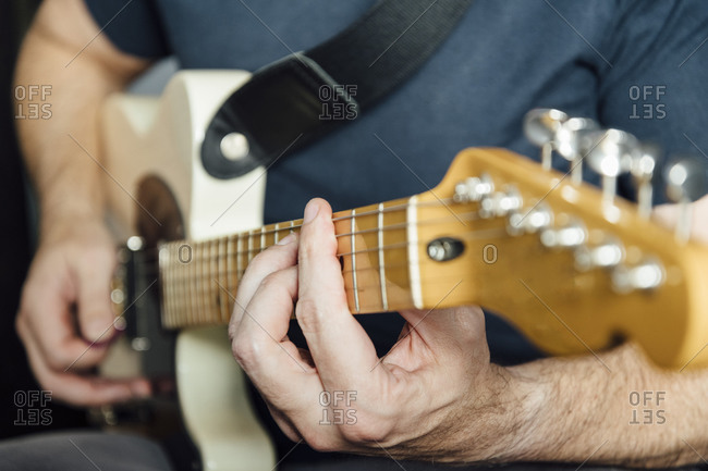 Man learning to play electric guitar