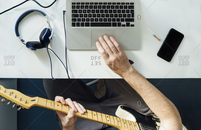 Top view of man learning to play guitar online using laptop