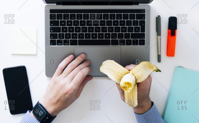 Spain- Hands of man typing on laptop and eating banana