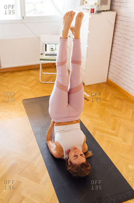 Woman practicing shoulder stand with feet up in exercise room at home