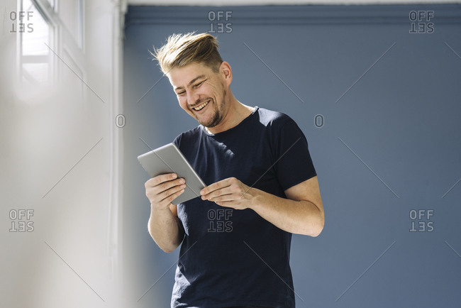 Happy man using a tablet at the window