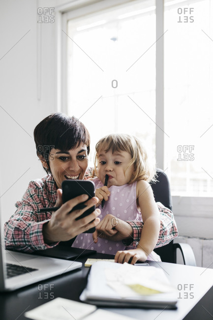 Mother and daughter using smartphone at home