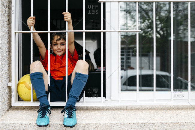 Boy with soccer ball at the window without being able to leave the house to play
