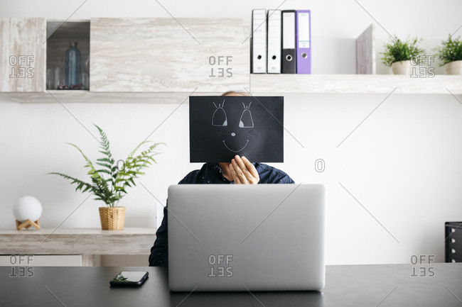 Man working at home with a black cardboard covering his face
