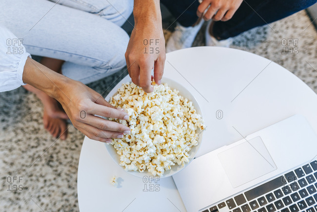 Low section of couple having popcorn by laptop at table in house