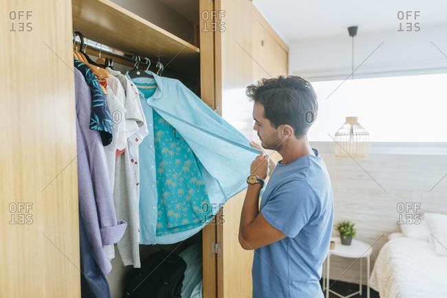 Young man choosing shirt from closet at home
