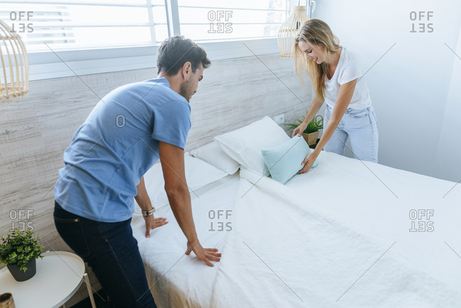 Happy couple arranging bed together at home.