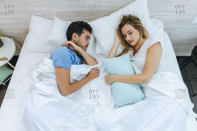 High angle view of couple sleeping on bed in bedroom at home