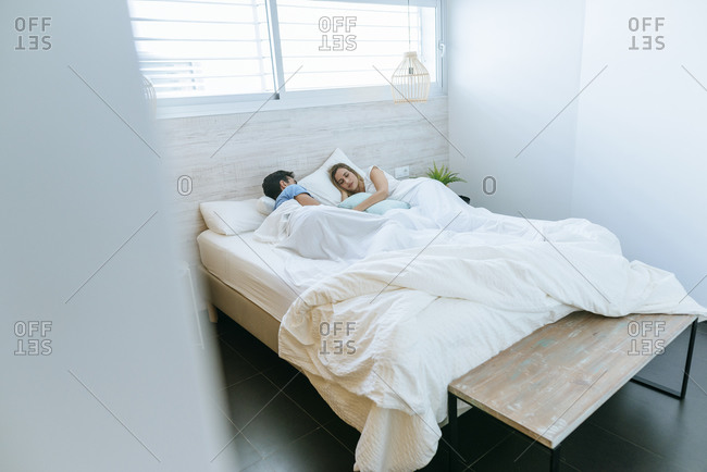 Couple sleeping on bed in bedroom at home