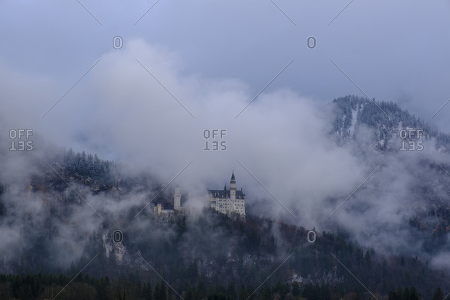 Germany- Bavaria- Hohenschwangau- Aerial view ofNeuschwanstein Castleshrouded in fog