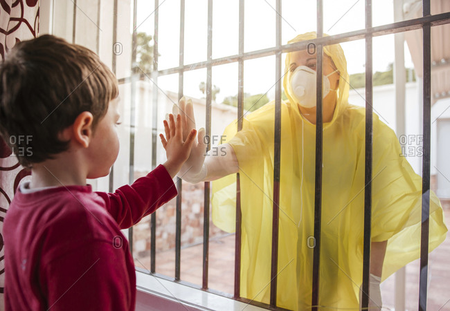 Boy touching mother's hand wearing protective clothing behind windowpane