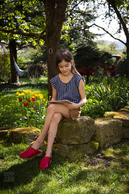 Smiling girl sitting in garden looking at digital tablet