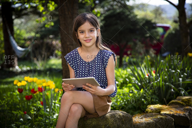 Portrait of smiling girl sitting in garden with digital tablet