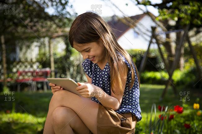 Happy girl sitting in garden using digital tablet