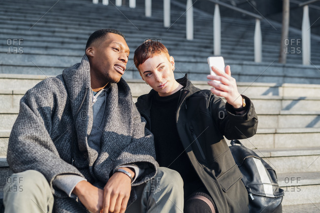 Young couple sitting on stairs in the city taking a selfie