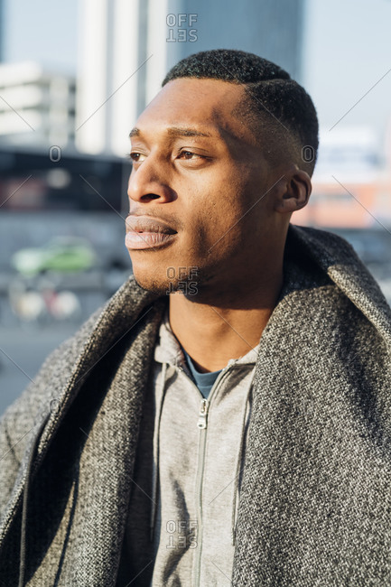 Portrait of young man in the city looking away