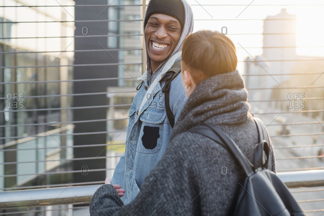 Happy young couple on a footbridge in the city at sunset