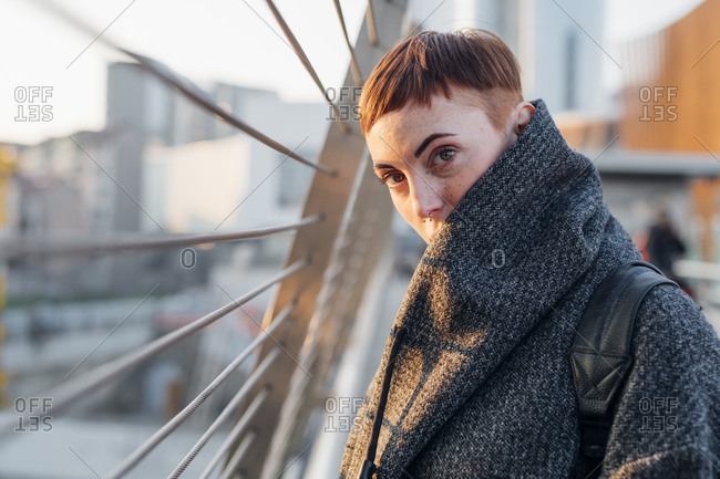 Portrait of redheaded young woman on a bridge in the city at sunset